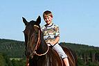 Junge sitzt auf Pferder�..